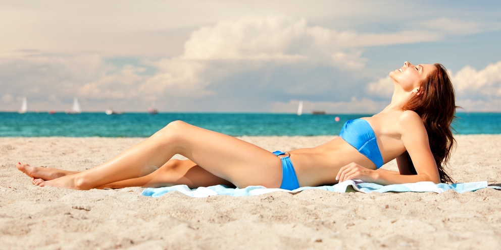 woman-lying-on-beach-towel-elite-daily
